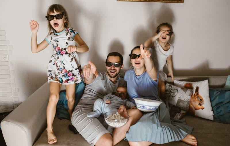 Todo el padre de la familia con el bebé en sus brazos, la madre y dos hijas en los vidrios especiales viendo la TV y comiendo las imagen de archivo