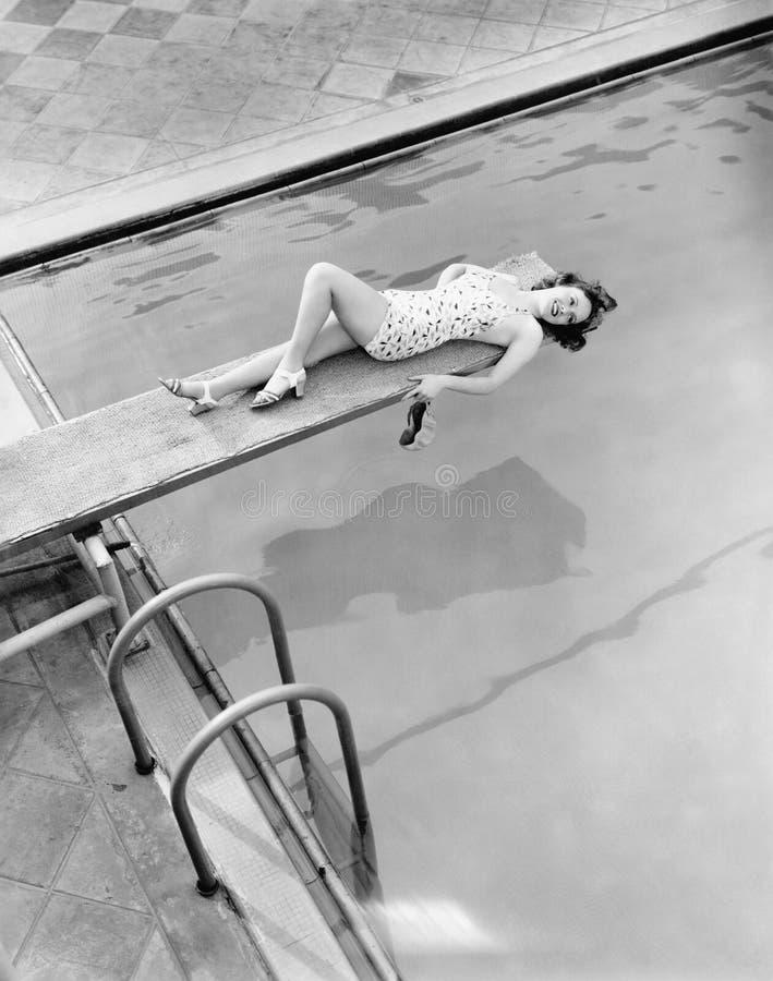 Todo está sobre el tablero para la mujer joven en la piscina (todas las personas representadas no son vivas más largo y ningún es fotografía de archivo