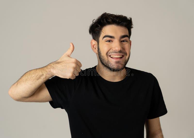Todo o grande! Homem considerável que faz os polegares acima dos gestos que sentem felizes e bem sucedidos fotos de stock royalty free
