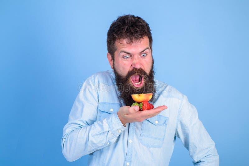 Todos para mí La cara hambrienta de grito del hombre con la barba come las invitaciones orgánicas Fresas y manzana barbudas de lo fotografía de archivo libre de regalías