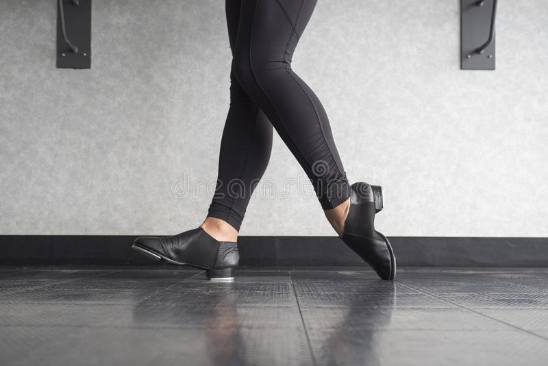 Toe Heel stand in tap shoes during dance class. Dancer performing a Toe Heel stand in tap shoes during dance class in the studio stock photo