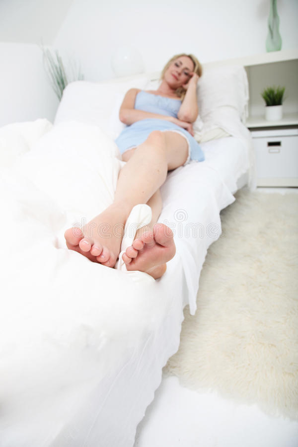 Toe to head view of woman on her bed royalty free stock image