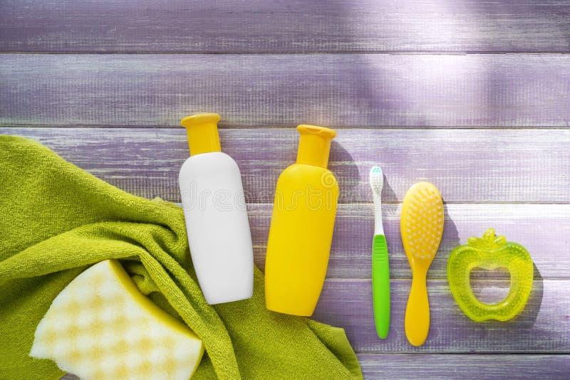 Toebehoren en schoonheidsmiddelen voor baby met handdoek op houten lijst royalty-vrije stock foto's