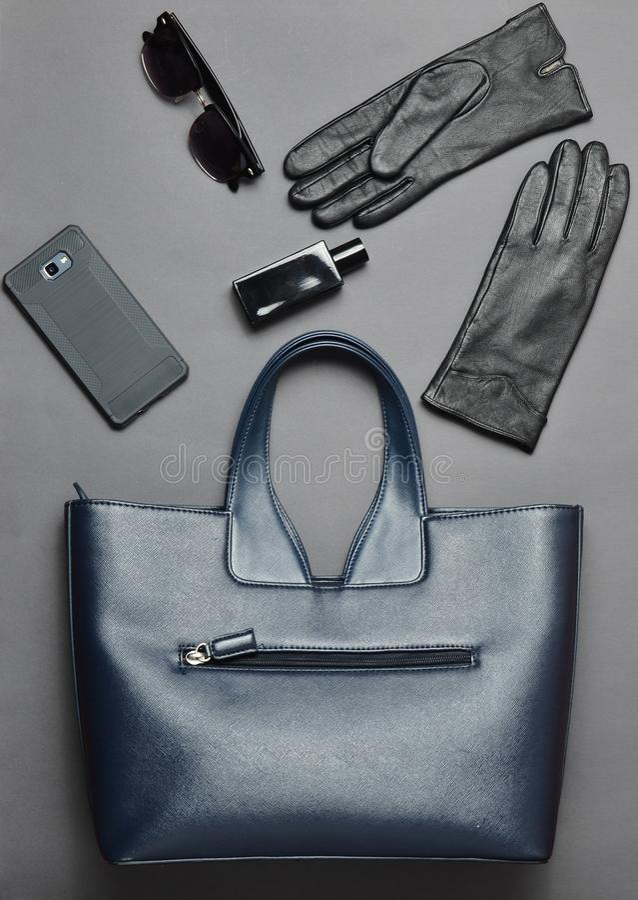 Toebehoren voor bedrijfsdame, gadgetslay-out op een grijze achtergrond, hoogste mening Leerzak, smartphone, zonnebril, handschoen stock afbeeldingen