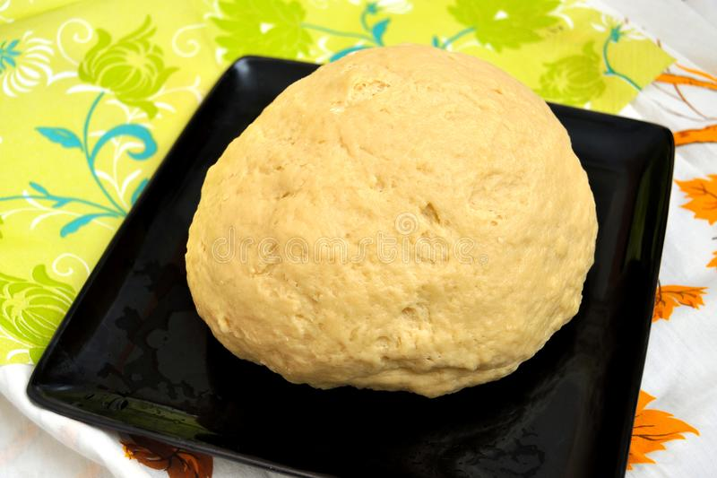 Toegenomen gistdeeg voor brood of pizza in een zwart bakseldienblad op een kleurentafelkleed stock foto