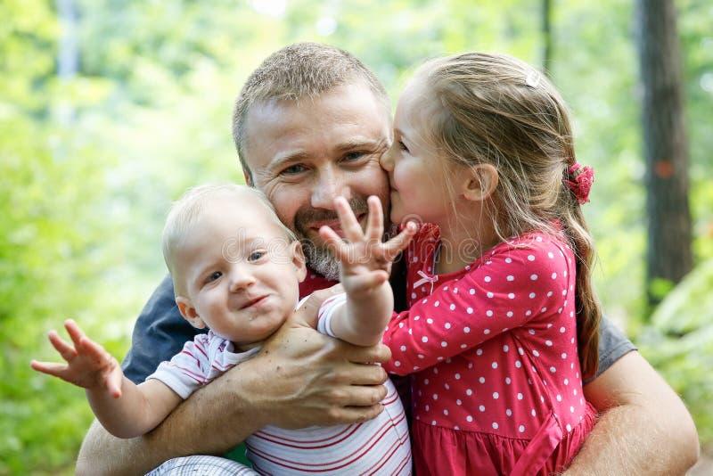 Toegewijde vader die zijn zoon en dochter koesteren, die van openlucht genieten stock afbeeldingen