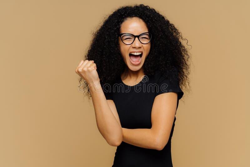 Toejuichen van optimistische vrouw klemt vuist dicht, luid schreeuwt, zijnd zeer emotioneel, steunt haar favoriet voetbalteam, dr stock afbeelding