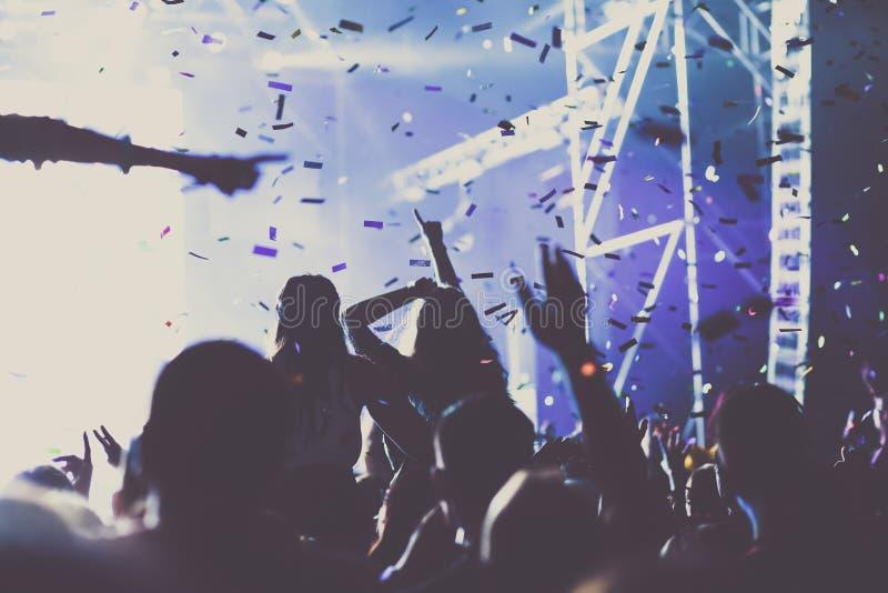 toejuichend menigte met opgeheven handen en vallend confettien bij overleg - muziekfestival royalty-vrije illustratie