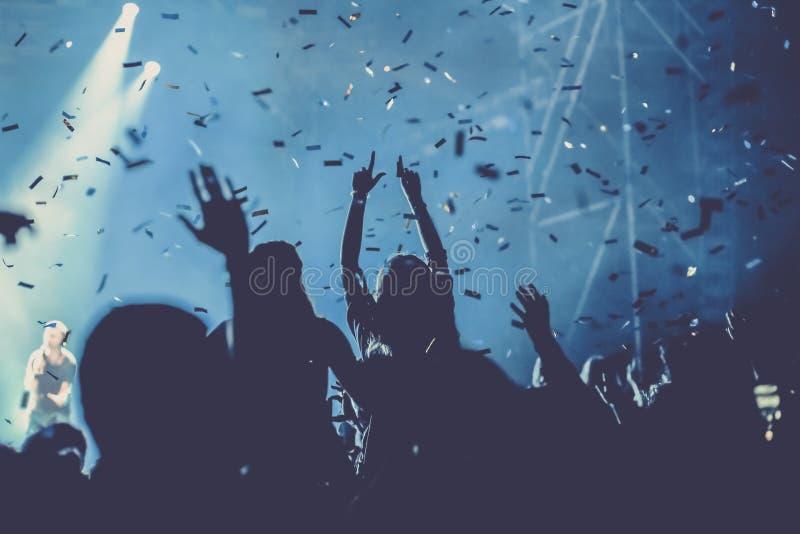 toejuichend menigte met opgeheven handen en vallend confettien bij overleg - muziekfestival stock illustratie
