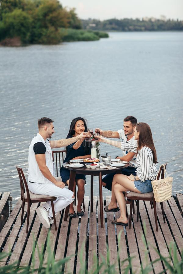 Toejuichingen! Groep vrienden die van openluchtpicknick in rivierpijler genieten royalty-vrije stock fotografie