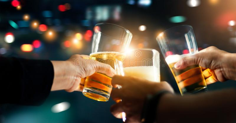 Toejuichingen het clinking van vrienden met bierdrank in partijnacht stock afbeelding