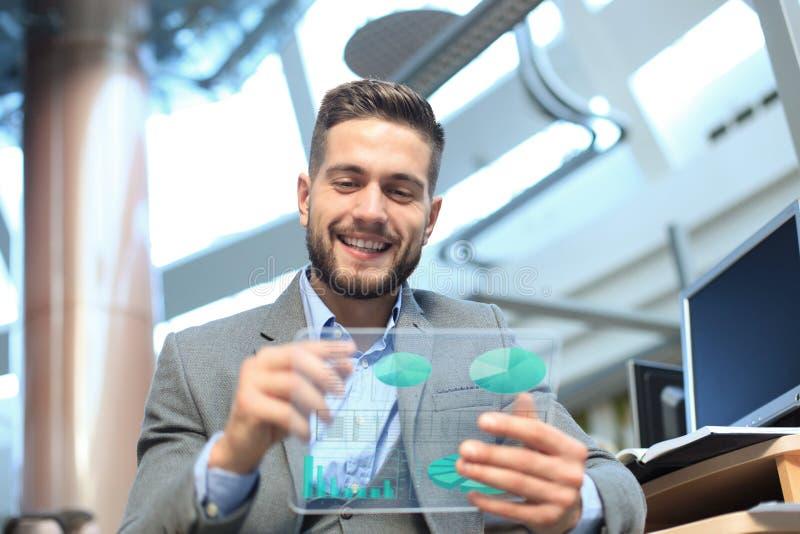 Toekomstig concept Zakenman die financi?le die statistieken analyseren op het futuristische transparante tabletscherm worden geto royalty-vrije stock fotografie
