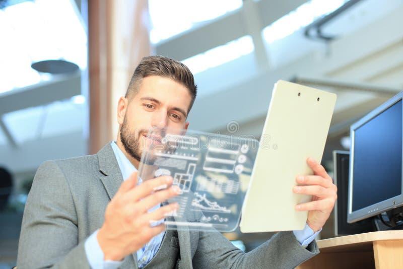 Toekomstig concept Zakenman die financi?le die statistieken analyseren op het futuristische transparante tabletscherm worden geto stock fotografie
