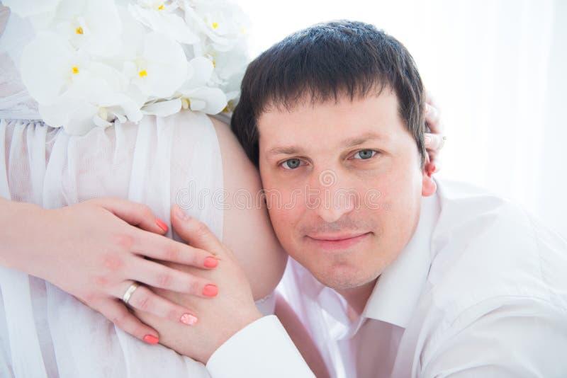 Toekomstige Gelukkige papa die zwangere buik, close-upportret koesteren stock foto