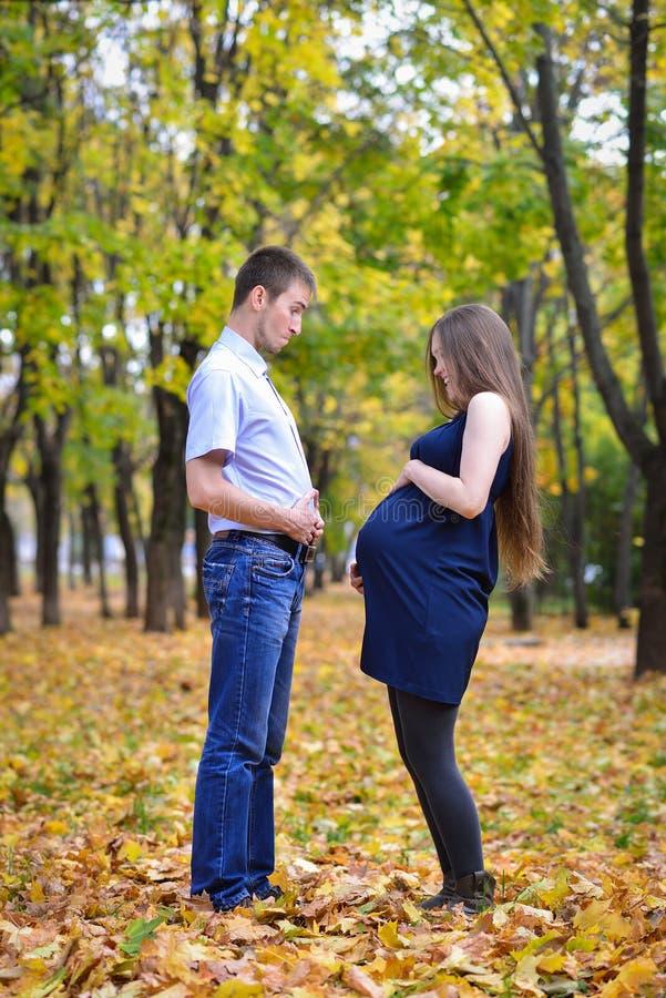 Toekomstige ouders, jonge man en zwangere vrouwen die pret in de herfstpark hebben royalty-vrije stock afbeeldingen