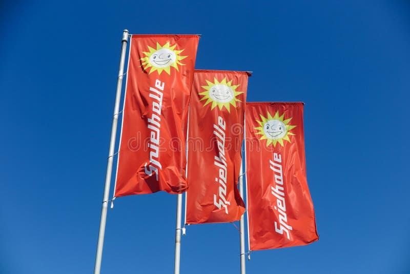TOENISVORST, GERMANIA - JUIN 28 2019: Chiuda su delle bandiere rosse contro cielo blu con il logo del sole del tedesco di Merkur  fotografia stock