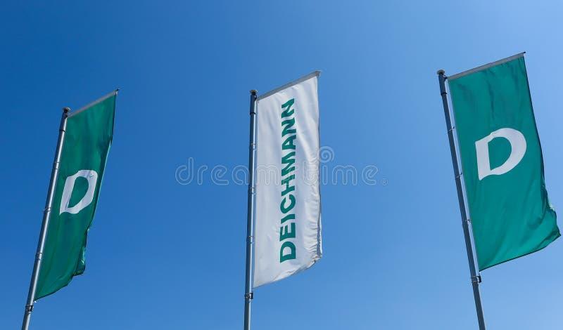 TOENISVORST, GERMANIA - JUIN 28 2019: Chiuda su delle bandiere rosse e verdi contro cielo blu della catena tedesca di Deichmann p fotografie stock libere da diritti