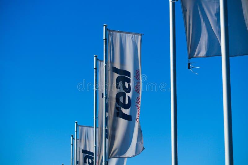 TOENISVORST, GERMANIA - 22 MARZO 2019: Bandiere con il logo della catena di supermercati tedesca reale contro chiaro cielo blu fotografie stock