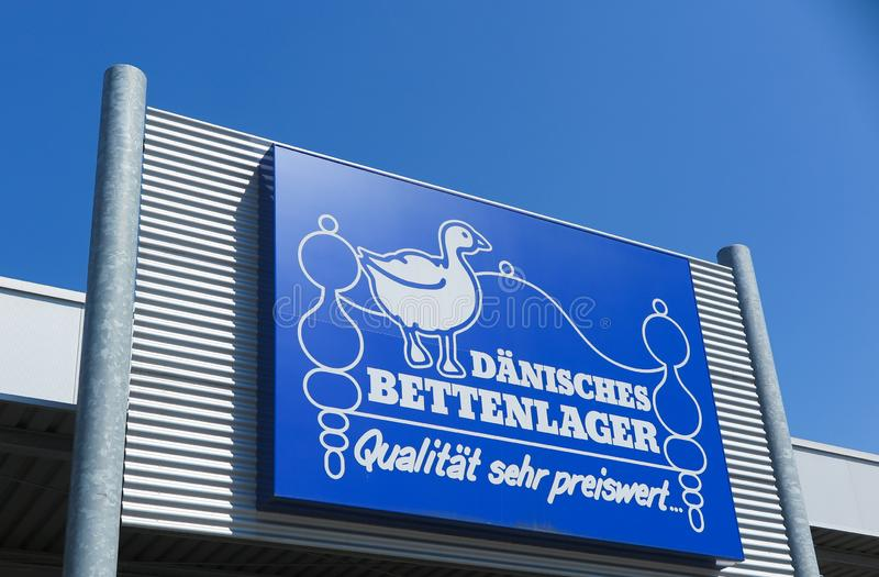 TOENISVORST, GERMANY - JUIN 28. 2019: Close up of blue logo against blue sky at store front of Dänisches daenisches Bettenlager royalty free stock images