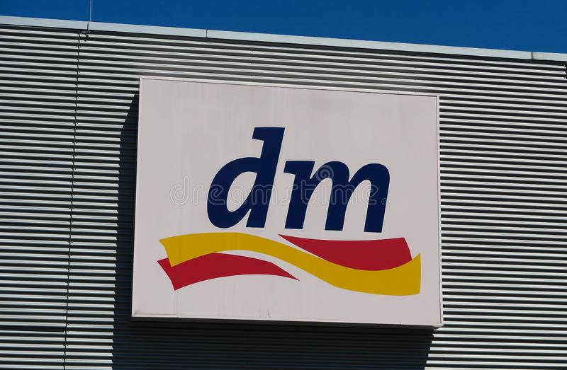 TOENISVORST, GERMANY - JUIN 28. 2019: Close up of logo of DM store on metal wall with blue sky german drugstore chain royalty free stock photography