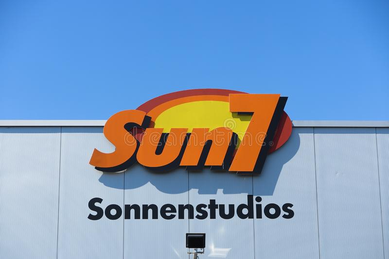 TOENISVORST, GERMANY - JUIN 28. 2019: Close up of orange and yellow logo of sun7 german tanning salon chain on wall against blue stock photos