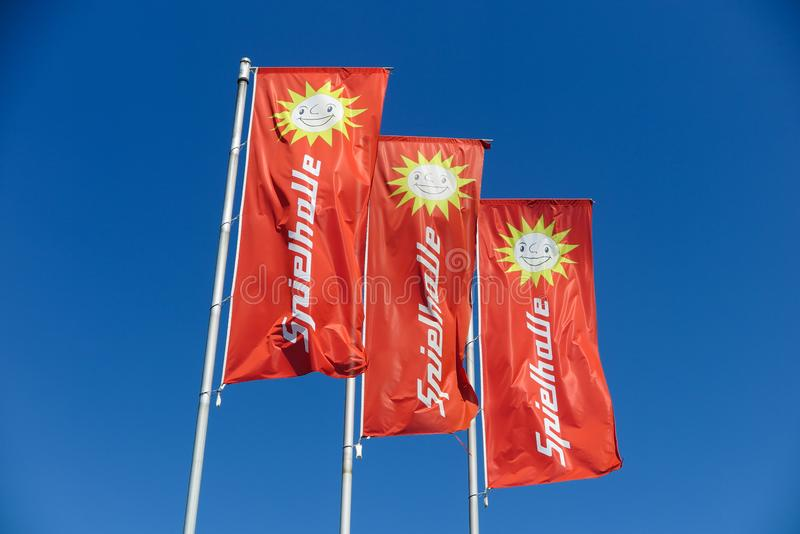 TOENISVORST, GERMANY - JUIN 28. 2019: Close up of red flags against blue sky with sun logo of Merkur Spielothek german gambling stock photography