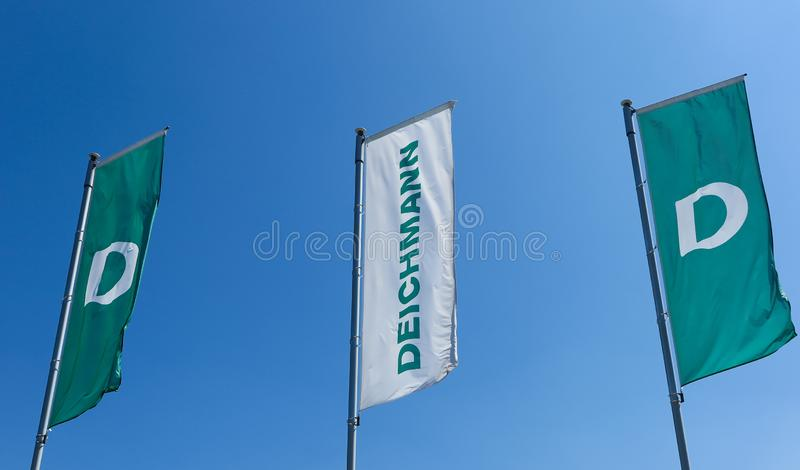TOENISVORST, GERMANY - JUIN 28. 2019: Close up of red and green flags against blue sky of Deichmann german chain for shoe fashion royalty free stock photos