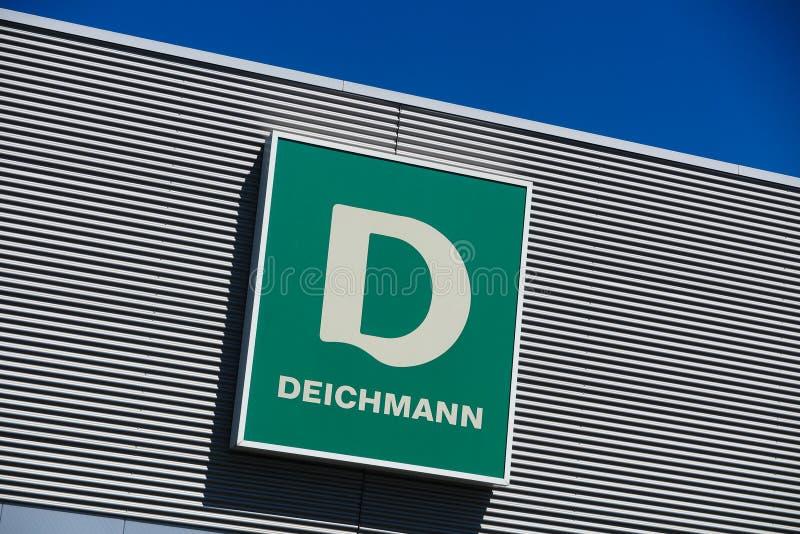 TOENISVORST TYSKLAND - JUIN 28 2019: Stäng sig upp av grön logo mot blå himmel på metallväggen av Deichmann den tyska kedjan för  arkivfoto