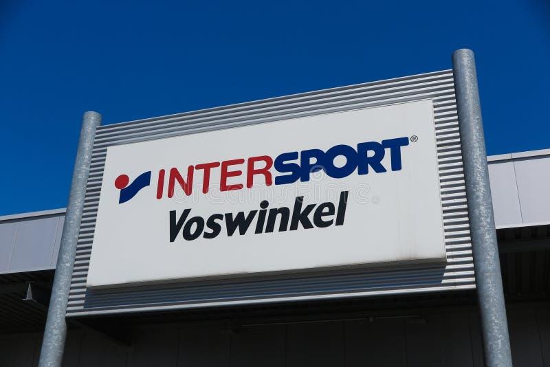 TOENISVORST TYSKLAND - JUIN 28 2019: Stäng sig upp av logo mot blå himmel av Intersport Vosswinkel den tyska kedjan för sporttill arkivfoton
