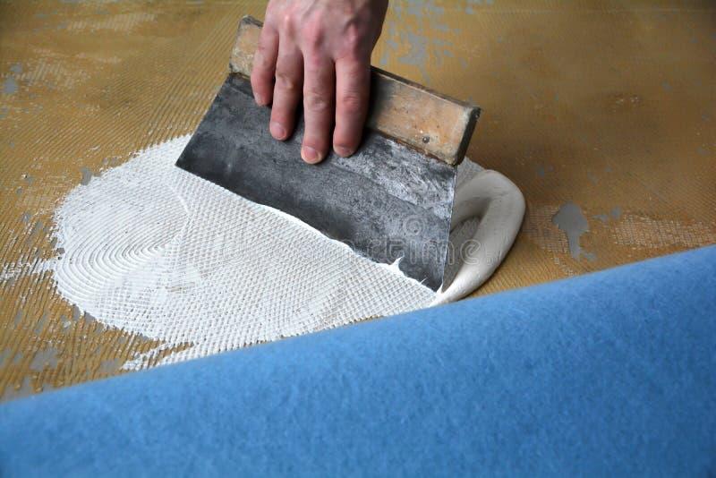 Toepassing van kleefstof voor het tapijt royalty-vrije stock fotografie
