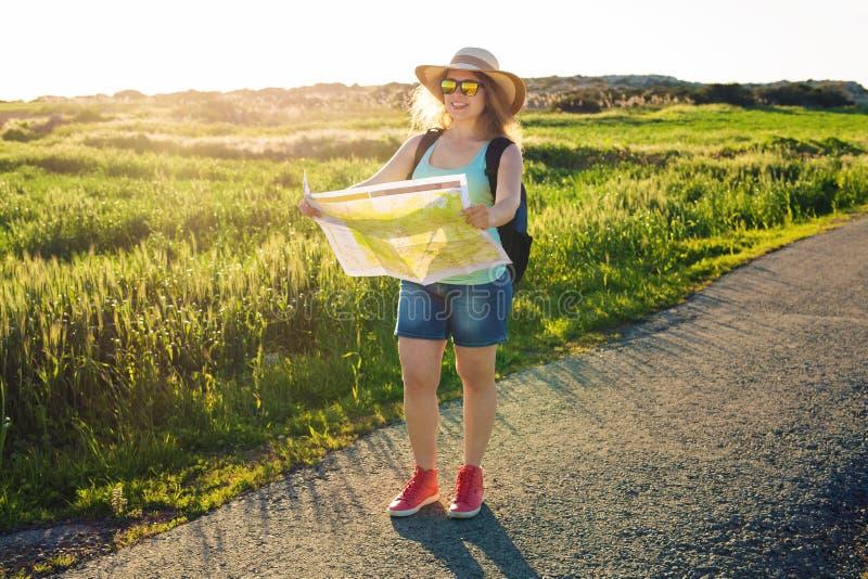 Toerisme, reis en de zomerconcept - de Gelukkige vrouwenreiziger met rugzak controleert kaart om richtingen te vinden royalty-vrije stock foto