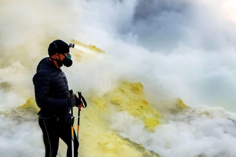 Toerist in beschermende kleding in de krater van een vulkaan Zwavelwolken, vulkanisch blauw meer en roze zonsopgang Een gevaarlij stock fotografie