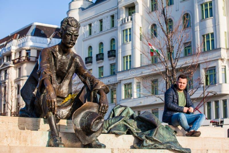 Toerist bij het zittingsstandbeeld van de Hongaarse dichter Attila Jozsef dichtbij het parlement in Boedapest stock foto's