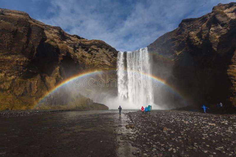 Toerist bij Skogafoss-waterval met dubbele regenboog onder blauwe sk royalty-vrije stock fotografie