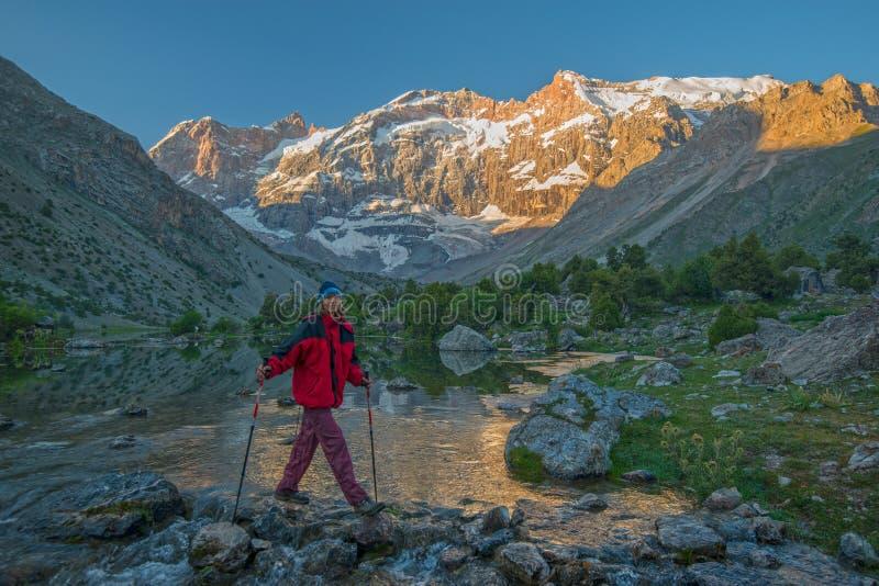 Toerist die bergrivier kruisen stock afbeelding