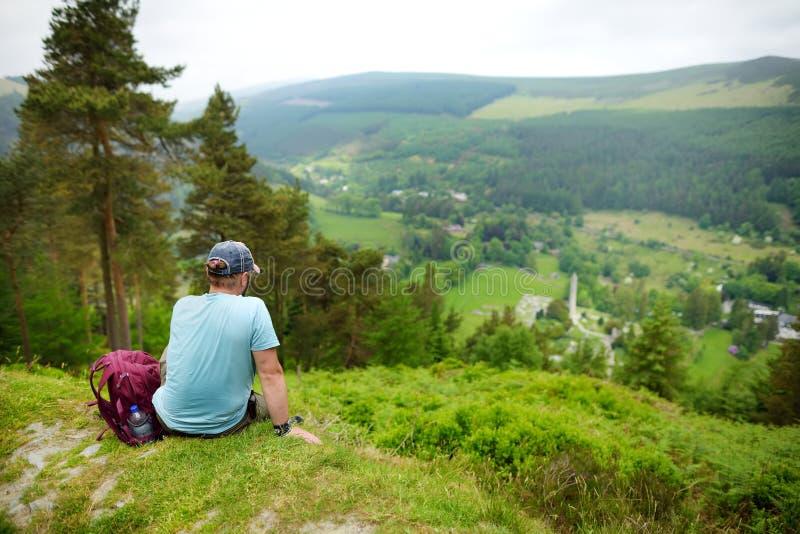 Toerist die de bossen van de Bergen Nationaal Park van Wicklow onderzoeken Oude pijnboombomen en weelderig groen van Glendalough- stock foto