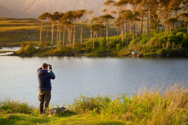 Toerist die de mening van Twaalf Pijnbomeneiland bewonderen, Connemara, Provincie Galway, Ierland stock foto