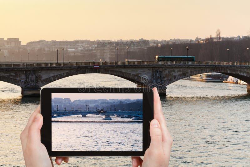 Toerist die foto van brug in Parijs op zonsondergang nemen stock foto's