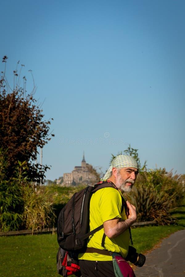 Toerist die met rugzak Mont Saint Michel bezoeken frankrijk stock foto's