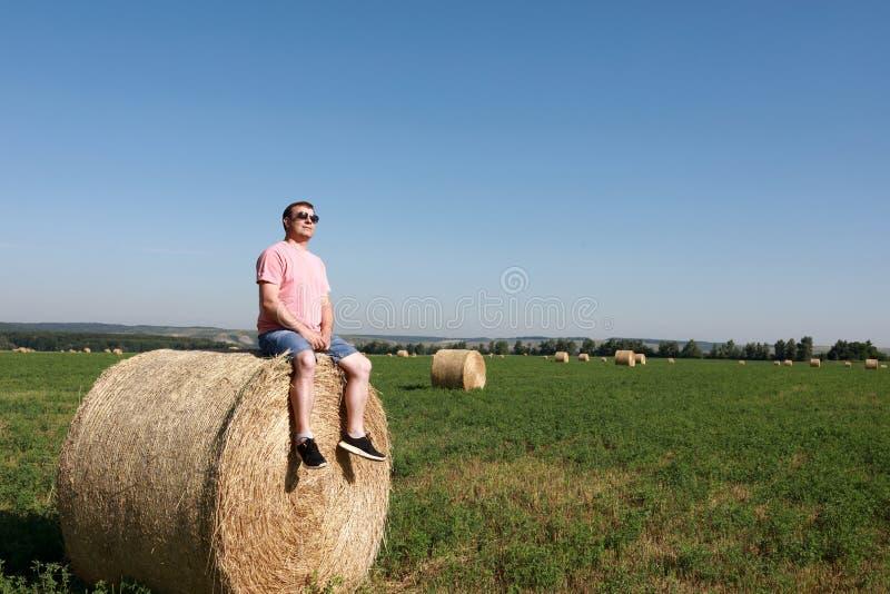 Toerist die op baal van stro rusten stock afbeelding