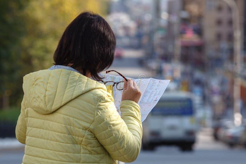 Toerist die op de kaart op de straat, op vakantie kijken stock foto