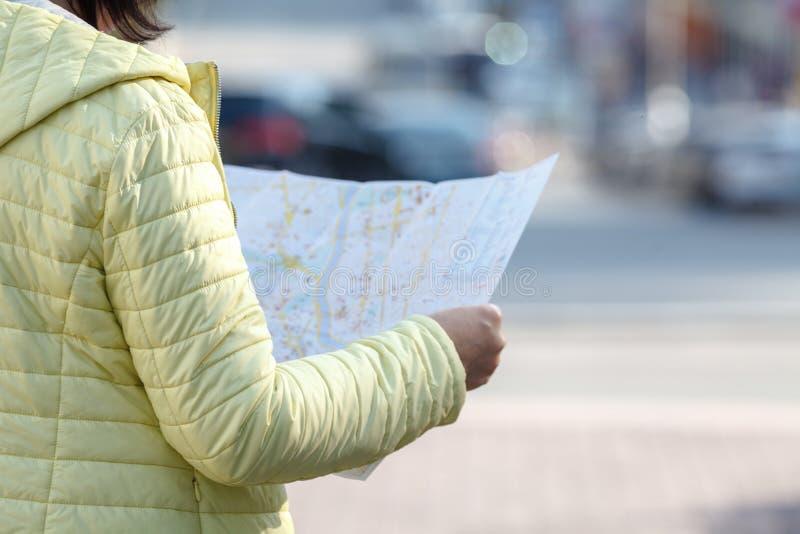 Toerist die op de kaart op de straat, op vakantie kijken stock fotografie