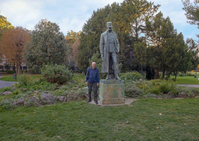 Toerist door de Keizer Francis Joseph I van het Bronsstandbeeld van Oostenrijk, Burggarten-Park, Wenen stock fotografie