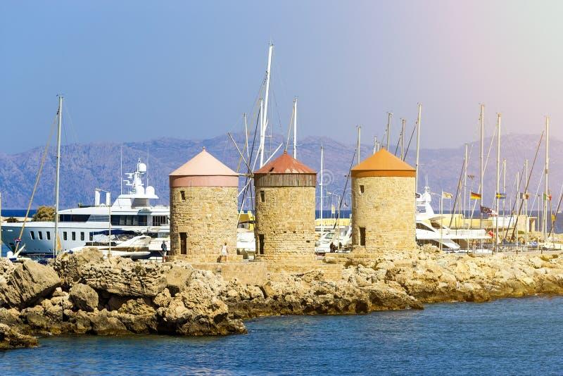 Toerist en geschiedenisoriëntatiepunten - Windmolens in Mandraki-zeehaven van Rhodos, Griekenland royalty-vrije stock afbeelding