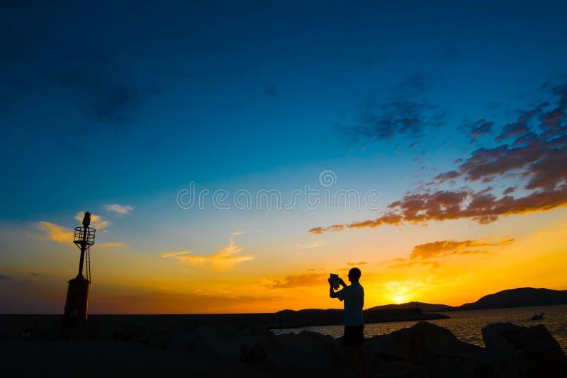 Download Toerist En Vuurtoren Bij Zonsondergang Stock Foto - Afbeelding bestaande uit vakantie, photographing: 54083418