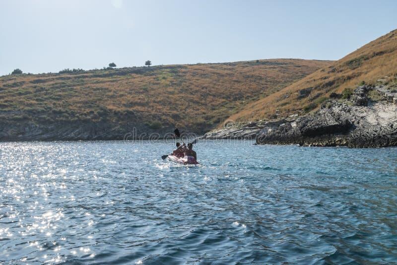 Toerist het kayaking bij de rotsachtige kust van Himara stock fotografie