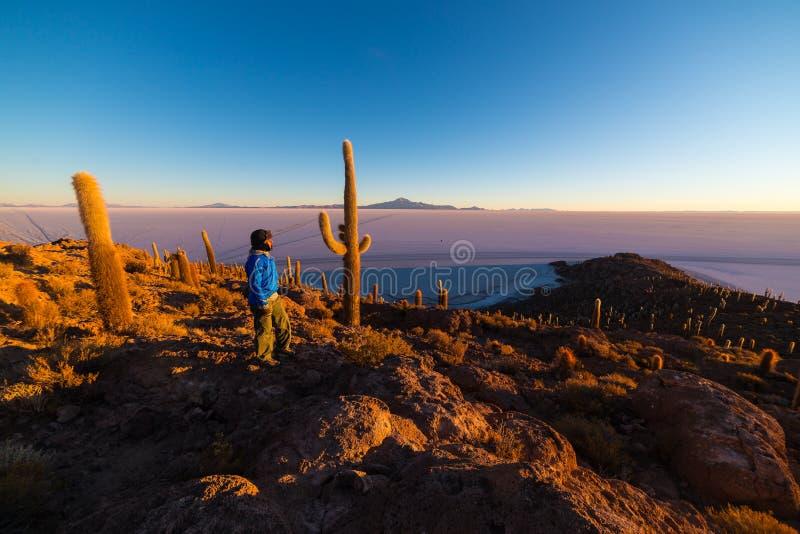 Toerist het letten op zonsopgang over de Zoute Vlakte van Uyuni, Bolivië royalty-vrije stock foto's