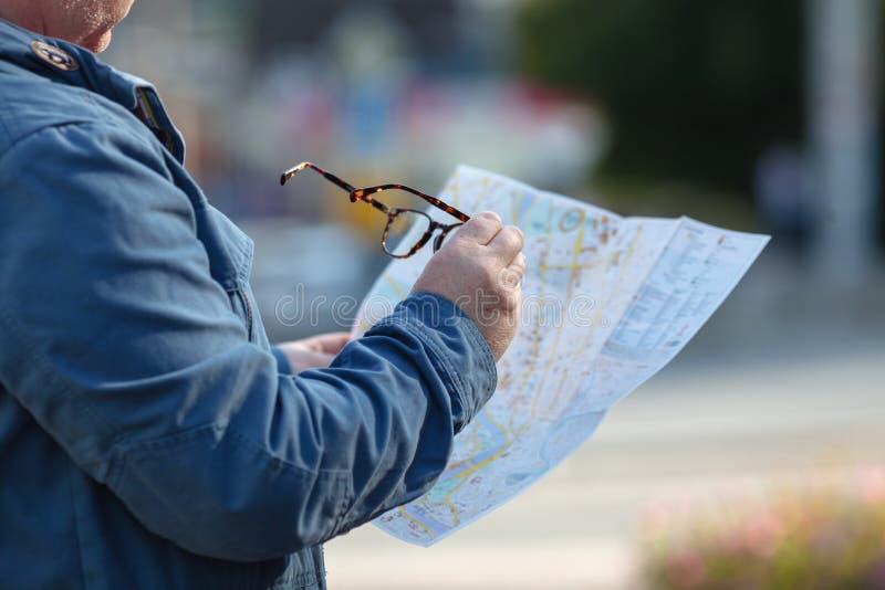 Toerist het loking op de kaart op de straat, op vakantie royalty-vrije stock afbeelding