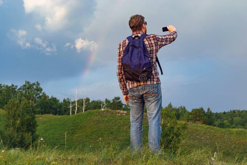 Toerist met de foto's van een rugzaklandschap stock afbeelding