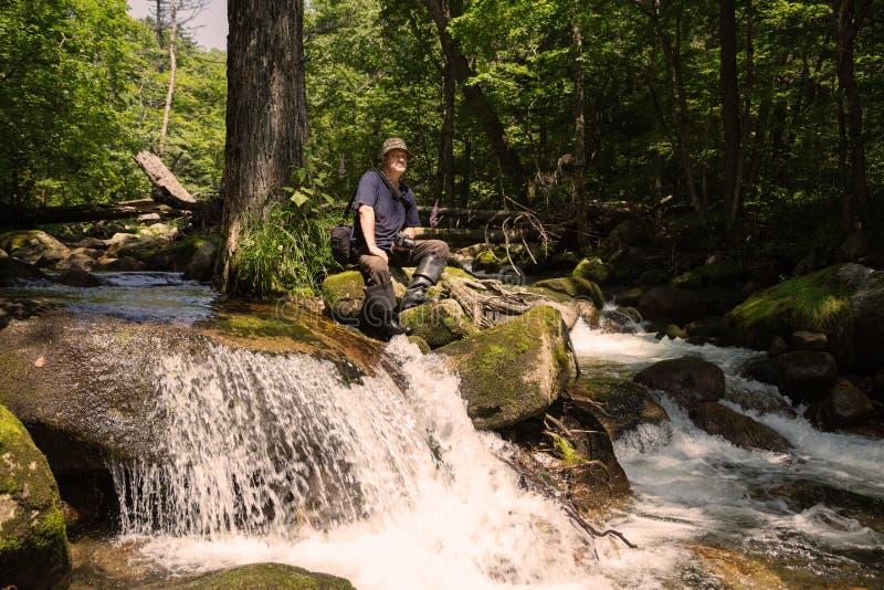 Toerist met een camerazitting op een steen dichtbij rivier royalty-vrije stock foto